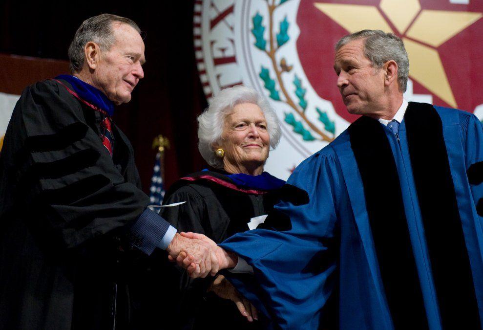 Presidente George W. Bush (derecha) le da la mano a su padre