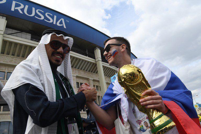 En las afueras del estadio Luzhiniki se saludan un hincha árabe y uno ruso.