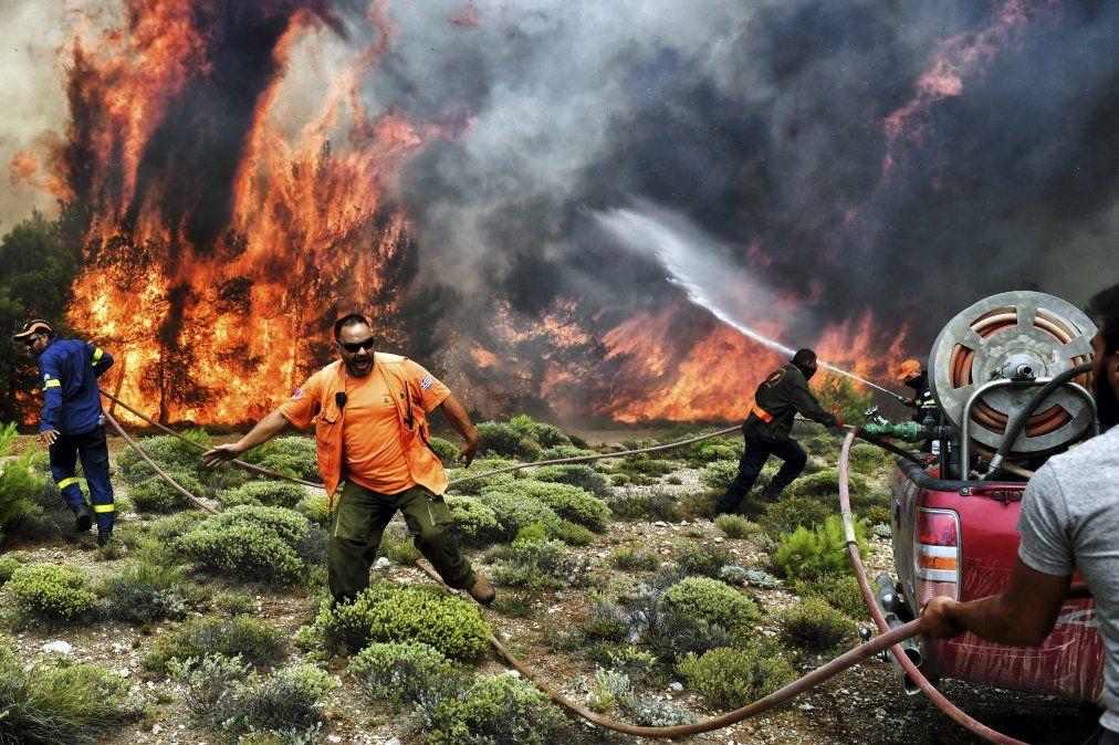 Bomberos y voluntarios intentan extinguir las llamas durante un incendio forestal en la aldea de Kineta