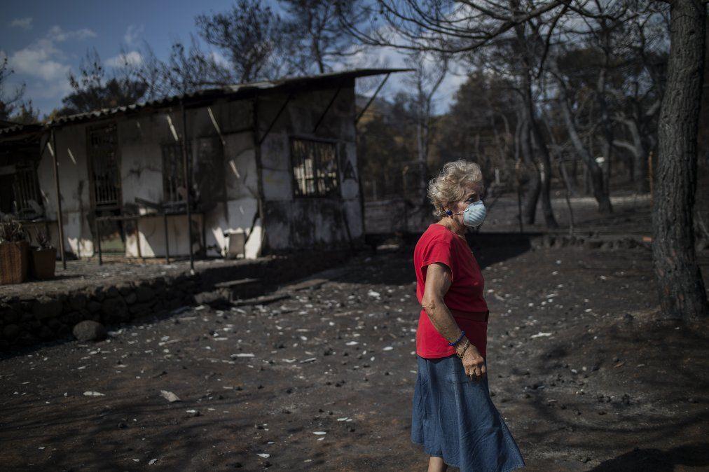 Una mujer usa una máscara frente a su casa incencendiada en Grecia