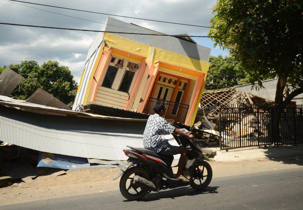 Un hombre en moto pasa frente a una casa dañada tras el sismo en Lombok