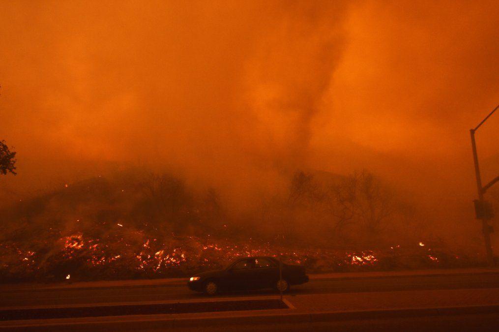 Un auto circula en un barrio residencial de California luego que el fuego alcanzara una ladera.