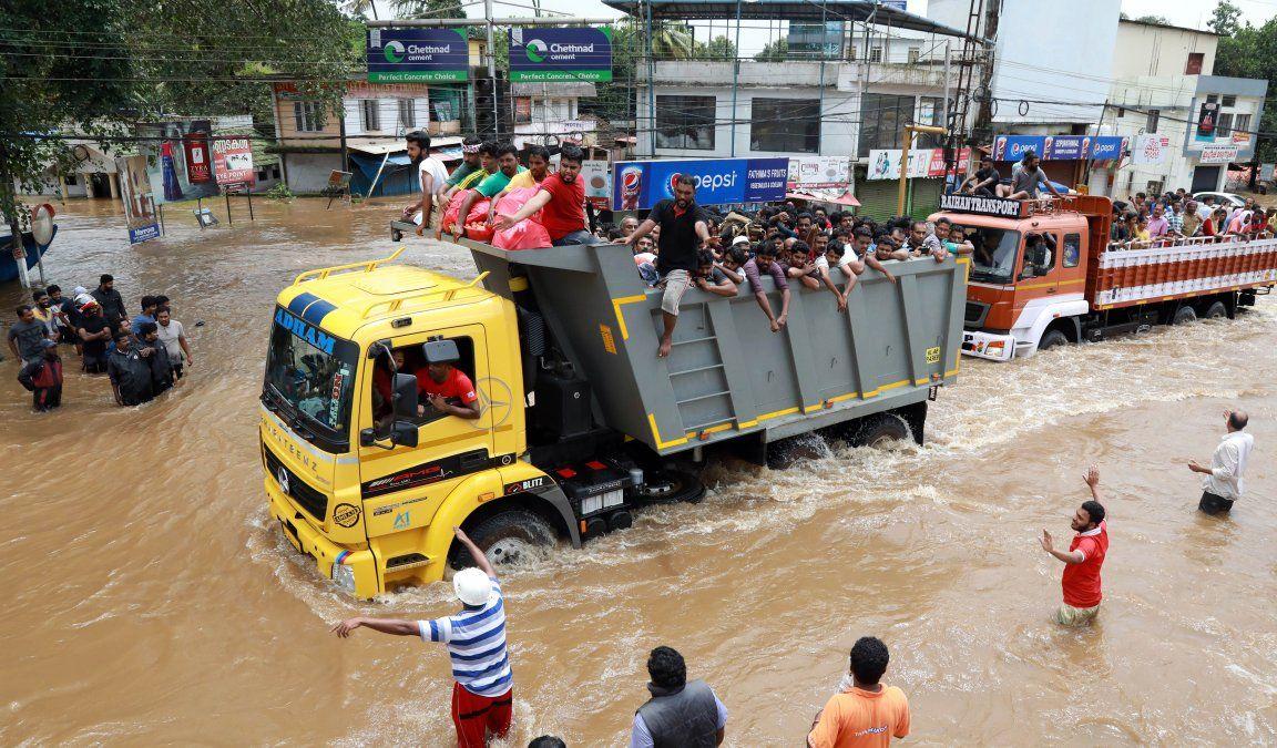 Pasajeros indios van en un camión hacia un lugar seguro mientras se han encontrado más de 100 cuerpos en un día por las inundaciones.