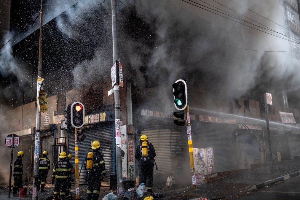 Bomberos tratan de extinguir el fuego en un edificio presuntamente secuestrado en el centro de Johannesburgo.