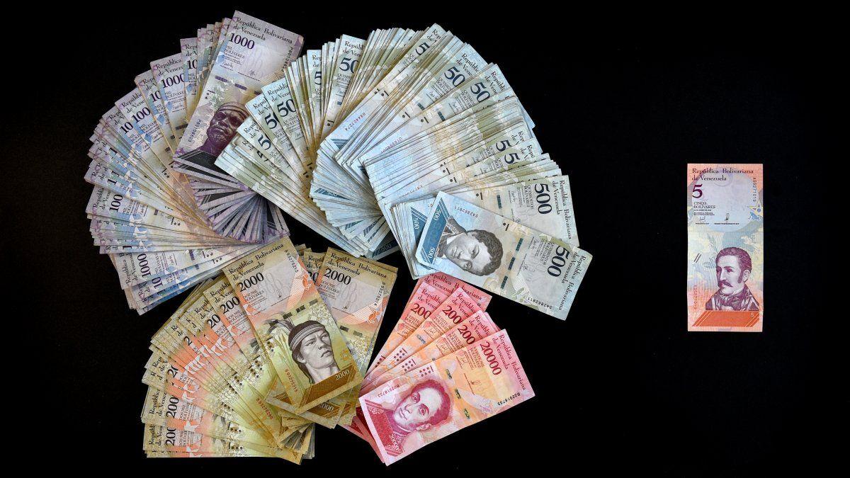 Un nuevo billete de 5 bolívares y su equivalente en billetes viejos luego que el banco quitara cinco ceros a la moneda.