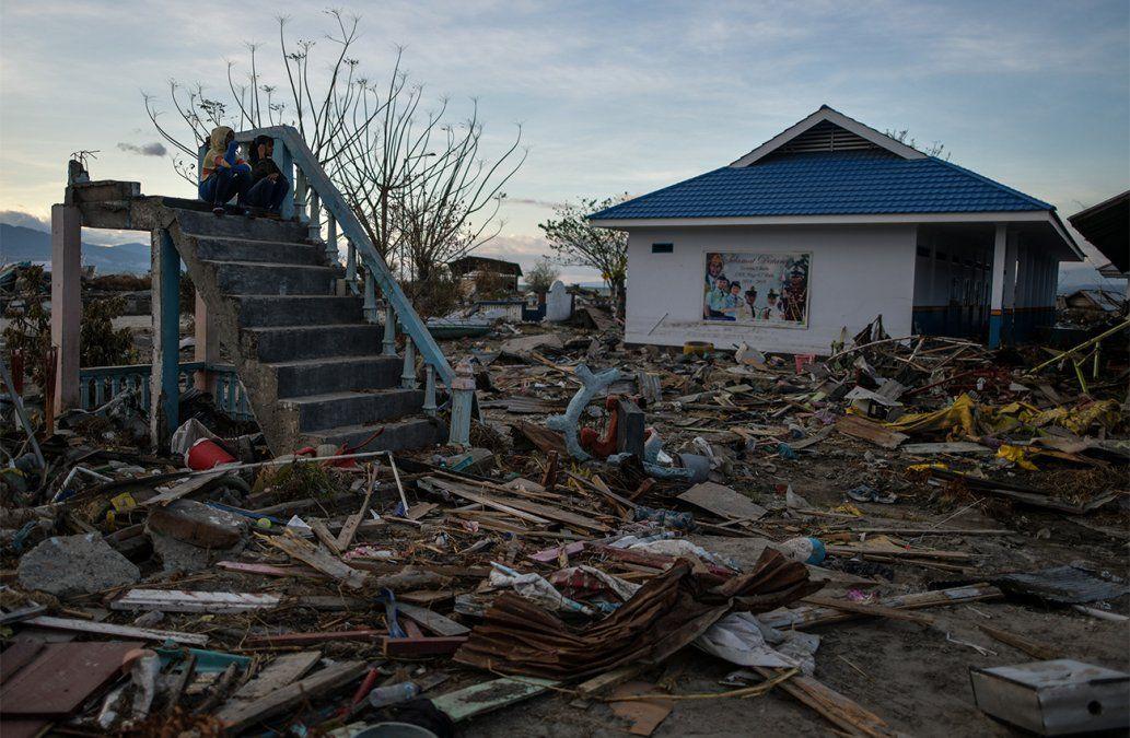 Dos mujeres se sientan en una dañada escalera de una escuela destruída por el tsunami en Palu