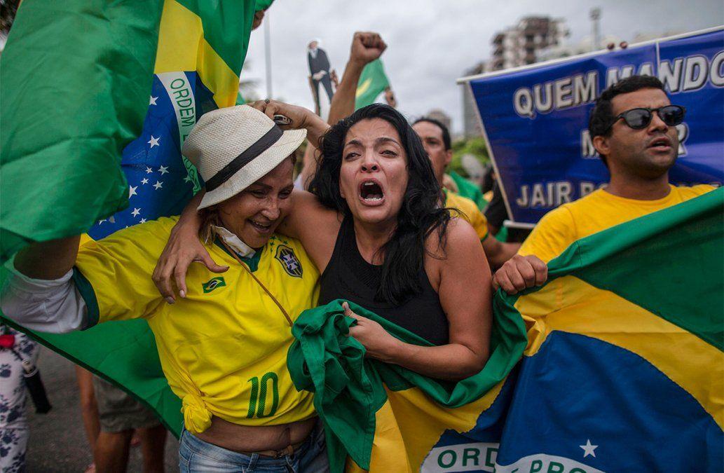 Simpatizantes del candidato del Partido Social Lineral Jair Bolsonaro celebran frente al condominio donde vive.