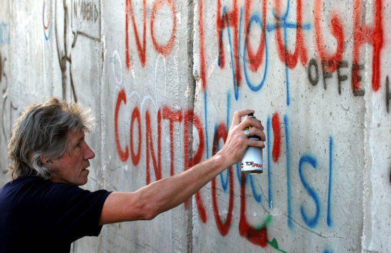 La leyenda del rock británico pinta un graffiti en el muro que rodea la ciudad Cisjordana de Belén el día antes de su concierto cerca de Tel Aviv