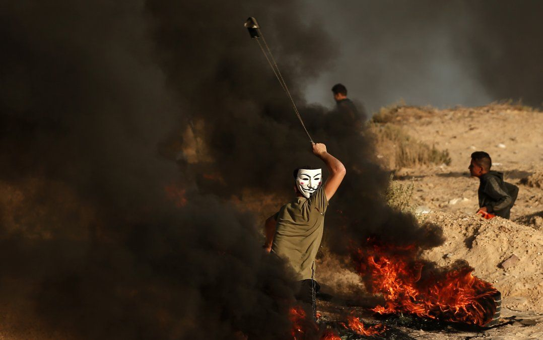 Un manifestante pelestino usa una honda para arrojar piedras durante una manifestación cerca de la frontera con Israel.