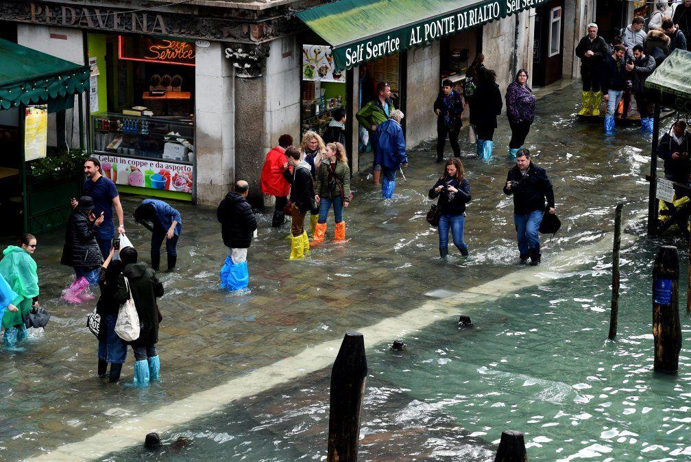 Turistas caminan en una calle inundada de Venecia