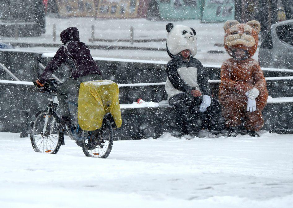 Un hombre en bicileta pasa al lado de dos personas disfrazadas de animales durante una fuerte nevada en Kiev