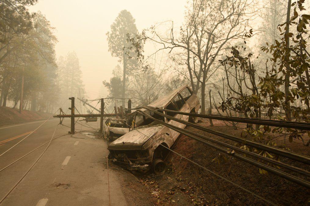 Una columna de energía eléctrica caída y un auto completamente quemado a un lado de la calle en Paradise
