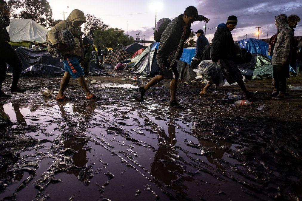 Migrantes centroamericanos acarrean sus pertenencias tras una fuerte lluvia en un refugio temporal en Tijuana.