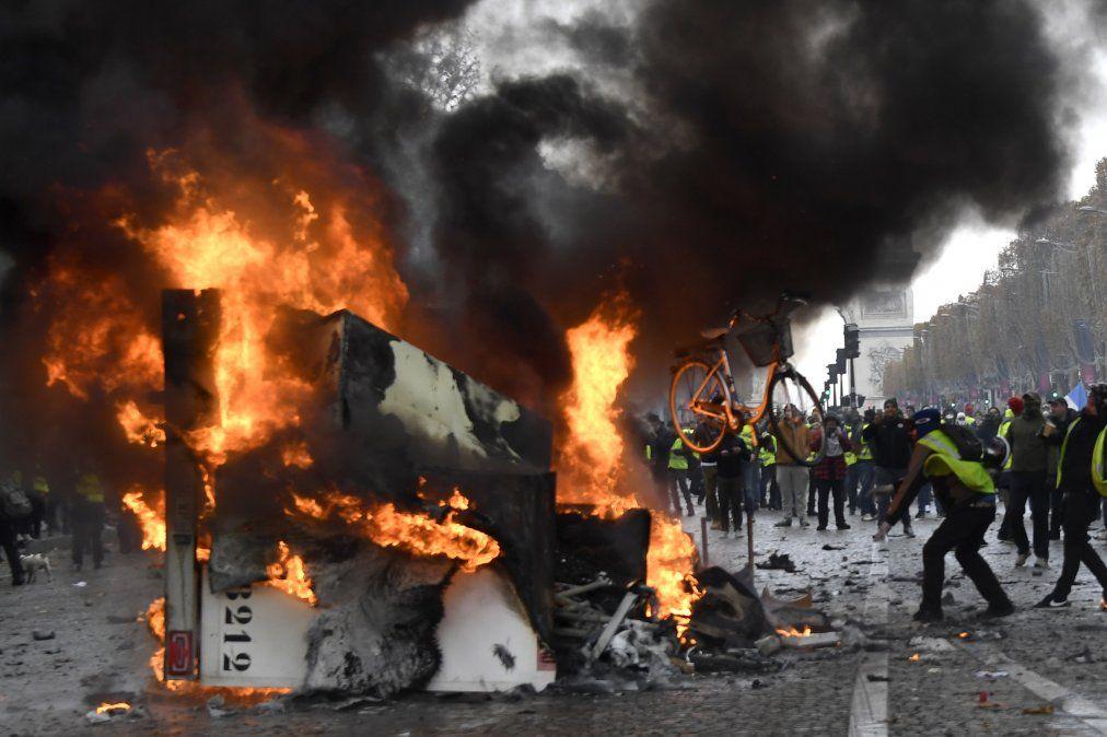 Un hombre lanza una bicicleta a un camión en llamas durante una protesta de los chalecos amarillos contra el aumento de precio del petróleo y del costo de vida cerca del Arco del Triunfo en París.