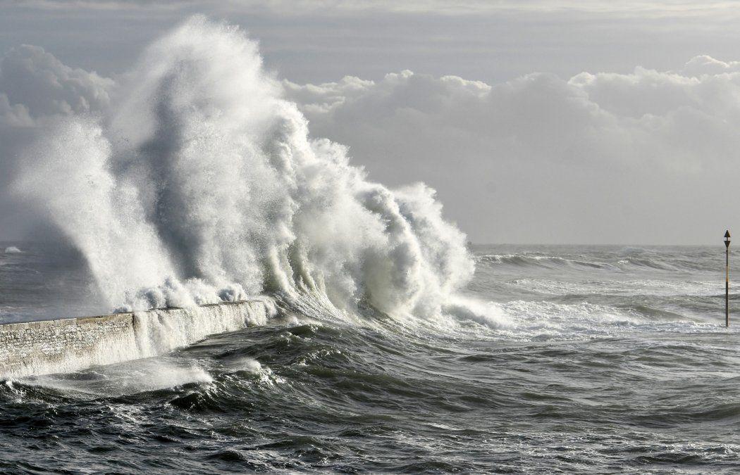 Las olas rompen en el embarcadero de Ploemeur