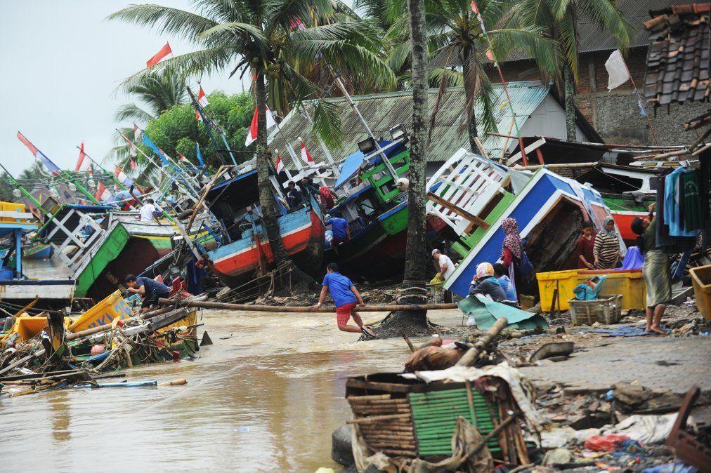Los pescadores atienden a sus barcos tradicionales que se dañaron después de ser golpeados por un tsunami en la aldea de Teluk