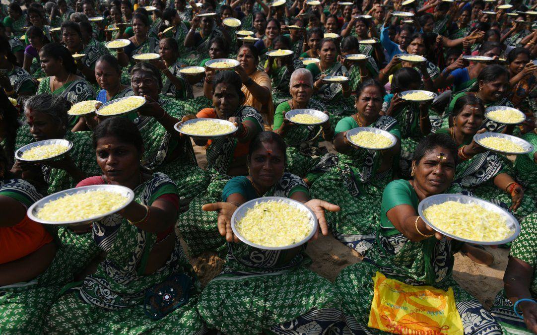 Mujeres indias posan mientras sostienen platos con pétalos de flores durante una ceremonia por las víctimas del tsunami de 2004
