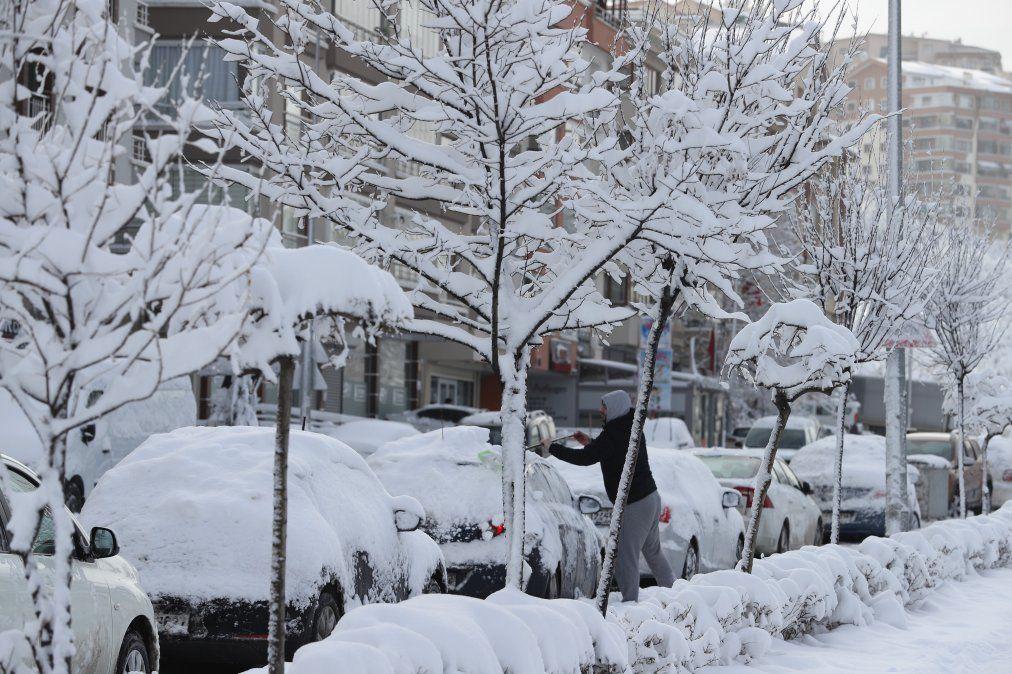 Un hombre remueve nieve de su auto en Ankara