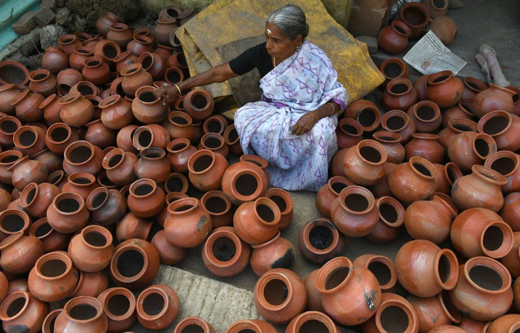 Una mujer india acomoda vasijas de barro para el festival Hindú Pongal.