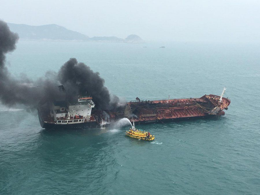 Un barco de bomberos lanza agua a un tanque de combustible encendido en llamas en la costa sur de Hong Kong.