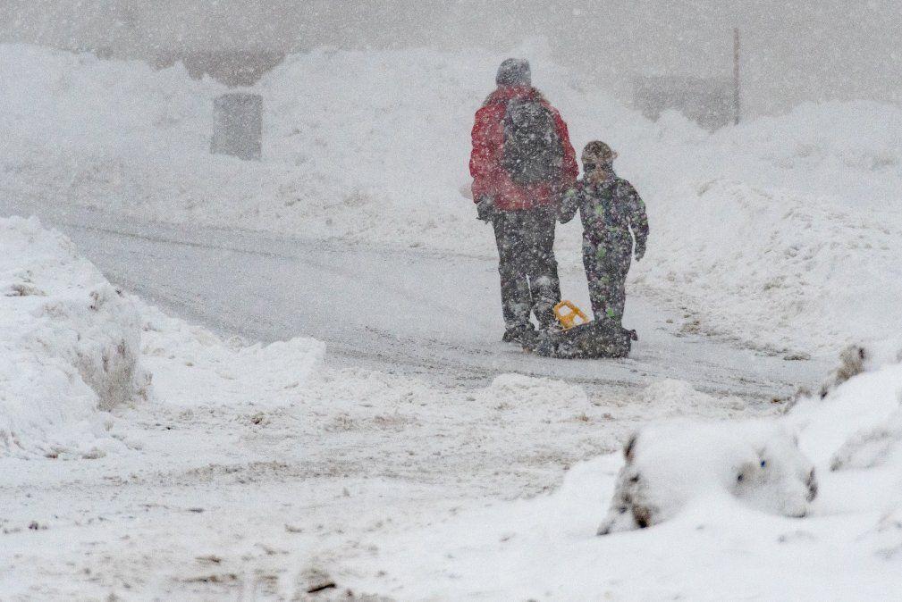 Una mujer y un niño caminan con un trineo a lo largo de una calle repleta de nieve en Sankt Englmar