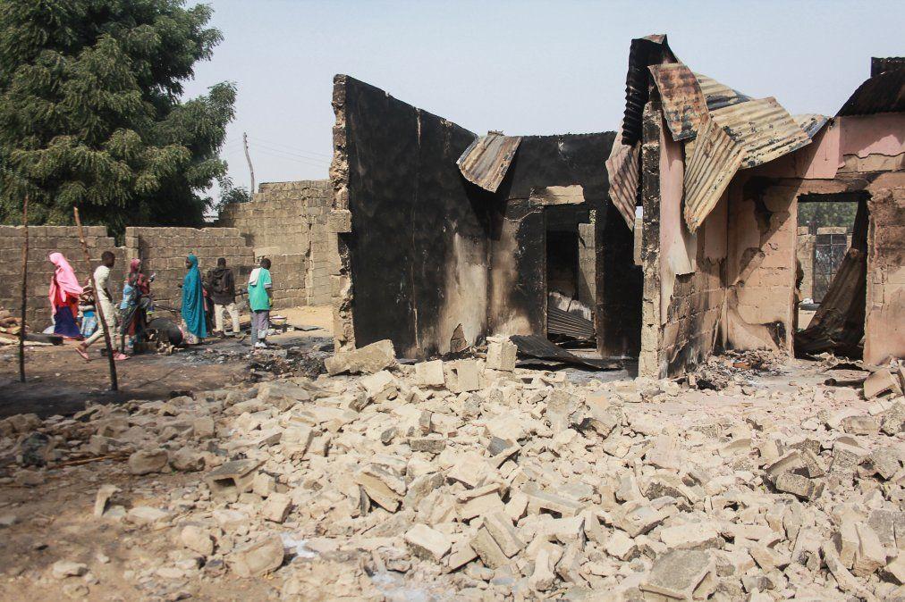 Un grupo de niños camina cerca de los restos de una casa tras un ataque en la villa Sajeri a manos del grupo armado Boko Haram.