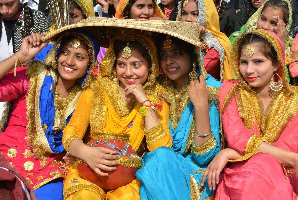 Escolares indias vestidas con trajes tradicionales Giddha posan para una foto antes de bailar danzas tradicionales.