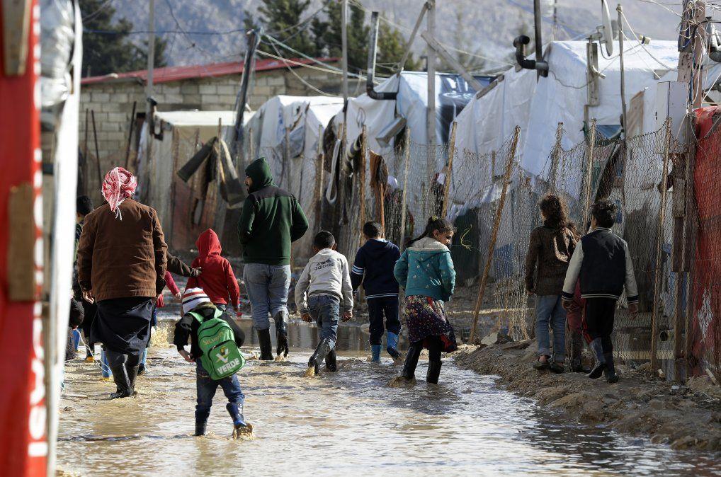Refugiados caminan sobre zonas inundadas y cubiertas de barro en un campamento de sirios tras las tormentas de invierno.