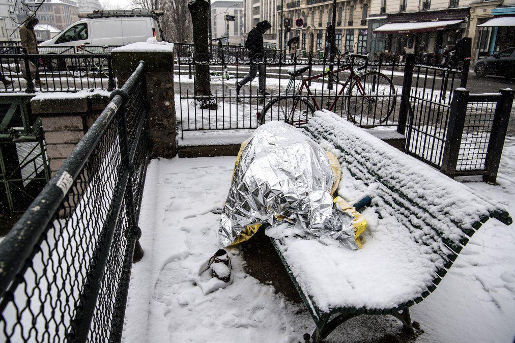 Un hombre sin techo duerme bajo mantas en un banco mientras la nieve cae sobre Paris.