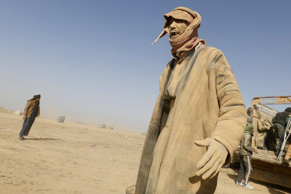 Un hombre cubierto de polvo hace gestos mientras personas huyen de las batallas entre las Fuerzas Democráticas de Siria y los combatientes del grupo Estado Islámico.