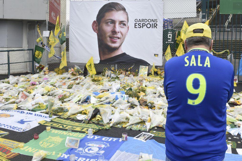Un simpatizante se para frente a las flores colocadas frente a un retrato gigante de Emilianio Sala afuera del estadio La Beaujoire