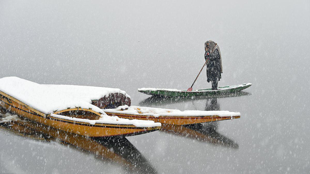 Un hombre de Kashmiri habla por celular, arriba de su barco, durante una nevada en el lago Dal en Srinagar el 7 de febrero de 2019