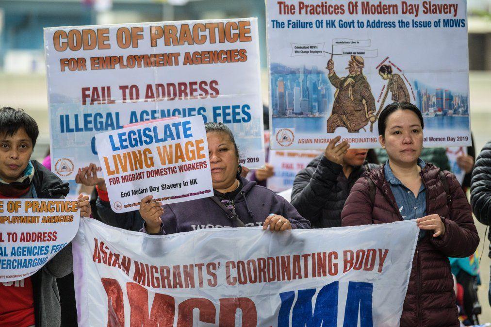 {altText(Empleadas domésticas migrantes y activistas sostienen pancartas mientras participan de la protesta en reclamo por mejores condiciones de trabajo para marcar el #8M.,Así se vive el Día Internacional de la Mujer en el mundo)}