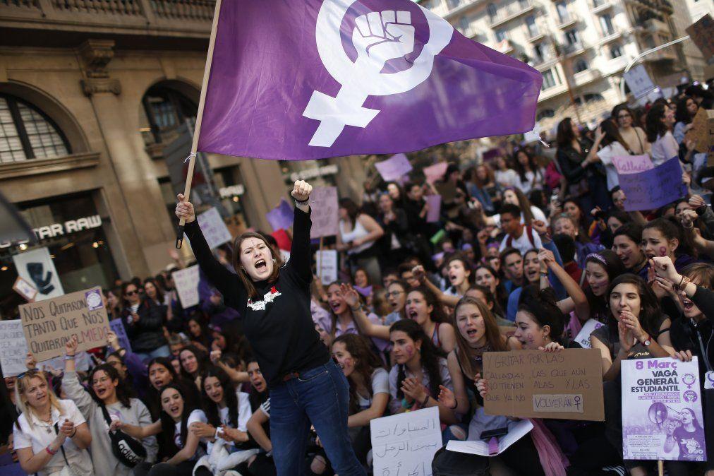 En España una mujer flamea una bandera feminista mientras los estudiantes gritan slogans por el Día Internacional de la Mujer.