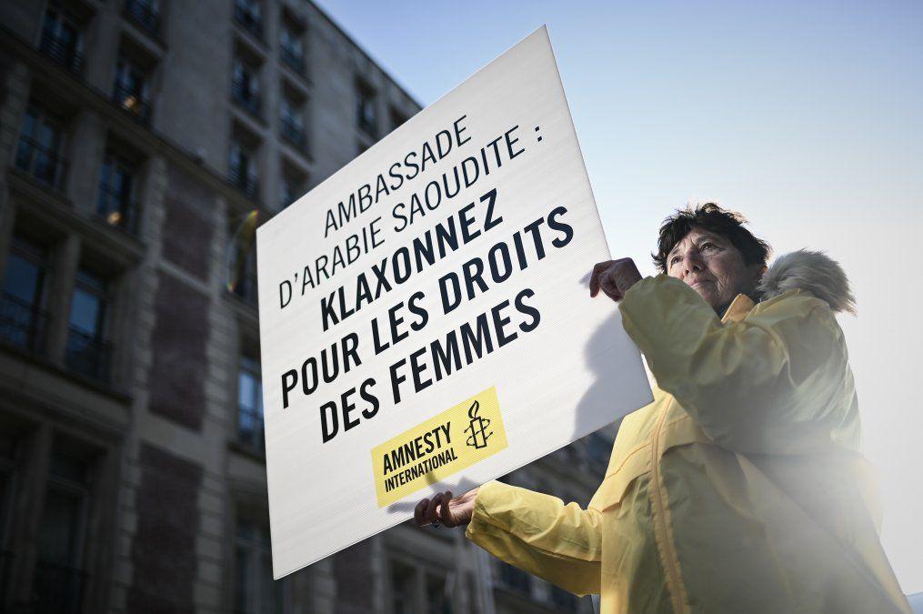 Una mujer sostiene un cartel que dice Embajada de Arabia Saudita: toque por los derechos de las mujeres mientras participa en una manifestación organizada por Amnistía Internacional fuera de la embajada de Arabia Saudita en París.