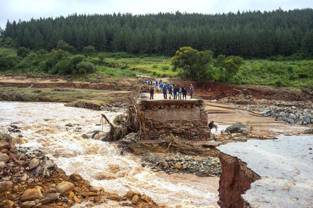 Trabajadores de la empresa Timber se quedan parados en un camino dañado luego que la zona fuera afectada por el ciclón que atravesó Mozambique y Zimbabwe.