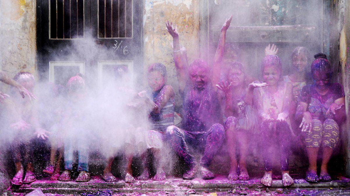 Niños de la India lanzan polvo de colores al aire durante las celebraciones por el Holi Festival en Chennai, que alude a la llegada de la primavera.