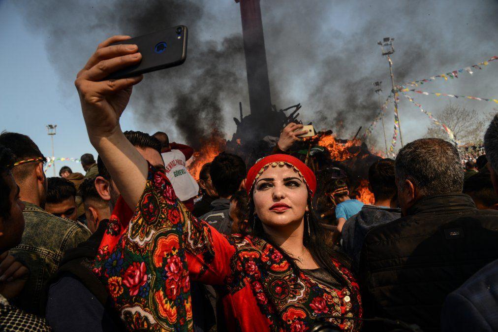 Una mujer se toma una selfie frente a una hoguera mientras los jurdos turcos se reúnen durante las celebraciones para el año nuevo