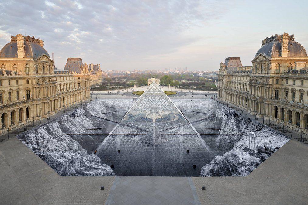 Un collage enorme del artista francés JR en la puerta de ingreso al museo Louvre en París para conmemorar el 30 aniversario de la pirámide.
