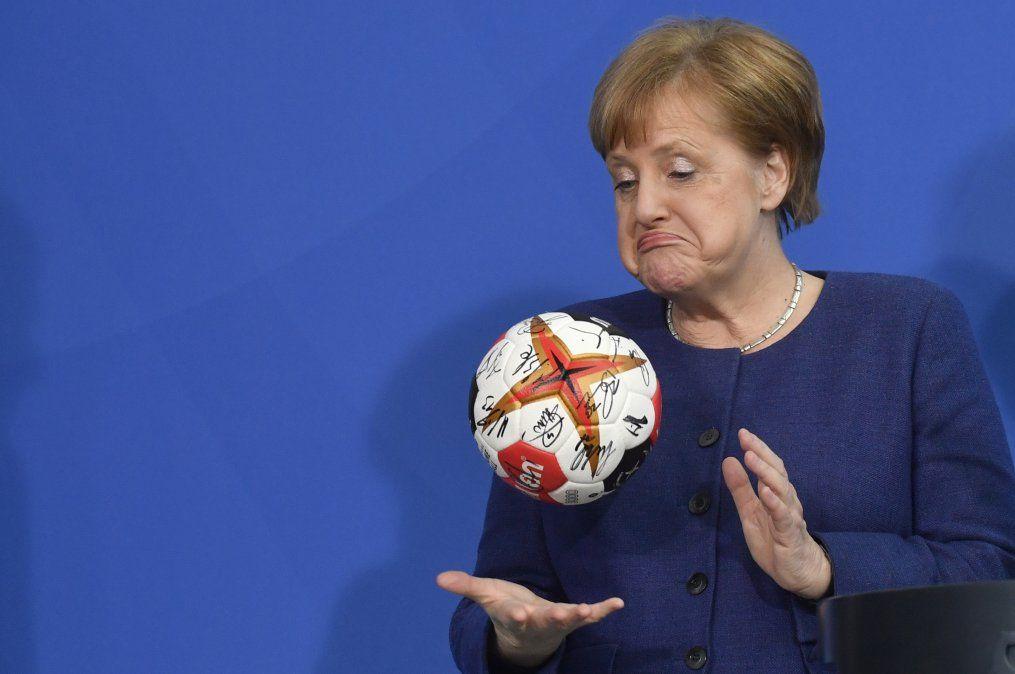 La canciller alemana Angela Merkel juega con una pelota dada a ella por la Federación Alemana de Handball.