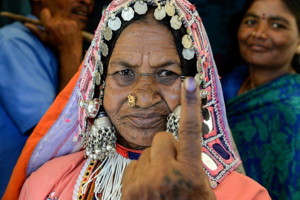 Una mujer indígena Iambadí muestra su dedo marcado con tinta después de votar durante las elecciones generales de la India