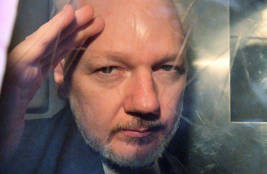 Assange hace gestos desde la ventana de una camioneta después de haber sido condenado a prisión.