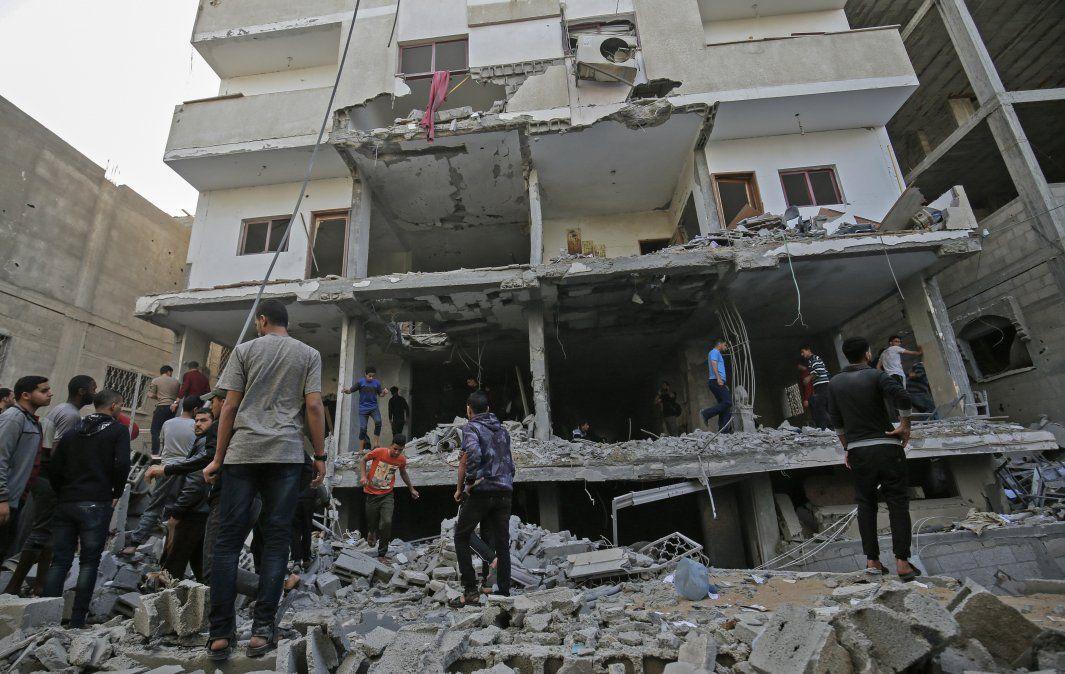 Palestinos revistan el daño en un edificio afectado por ataques aéreos al Sur de la Franja de Gaza.