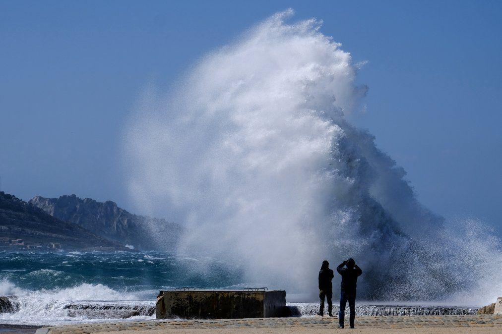 Personas miran las fuertes olas golpeando la orilla en la Playa de David en Marsella