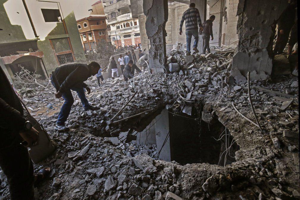 Palestinos revisan los daños en un edificio destruido luego de los ataques aéreos israelíes