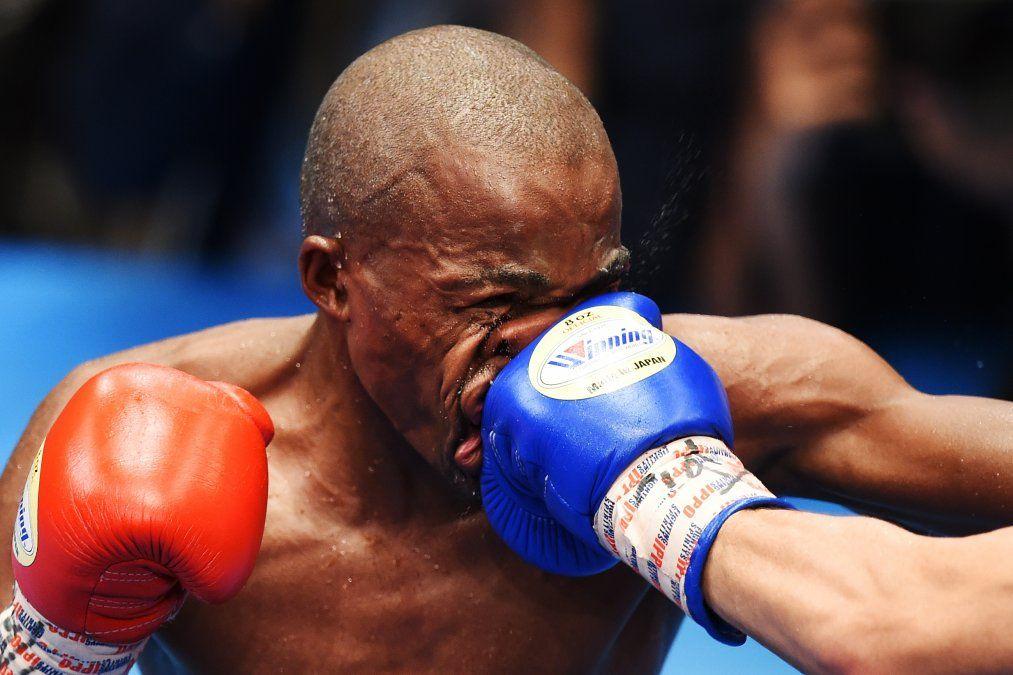 Moruti Mthalane de Sudáfrica es golpeado por Masayuki Kuroda de Japón durante la pelea por el título de peso mosca de la FIB en Tokio