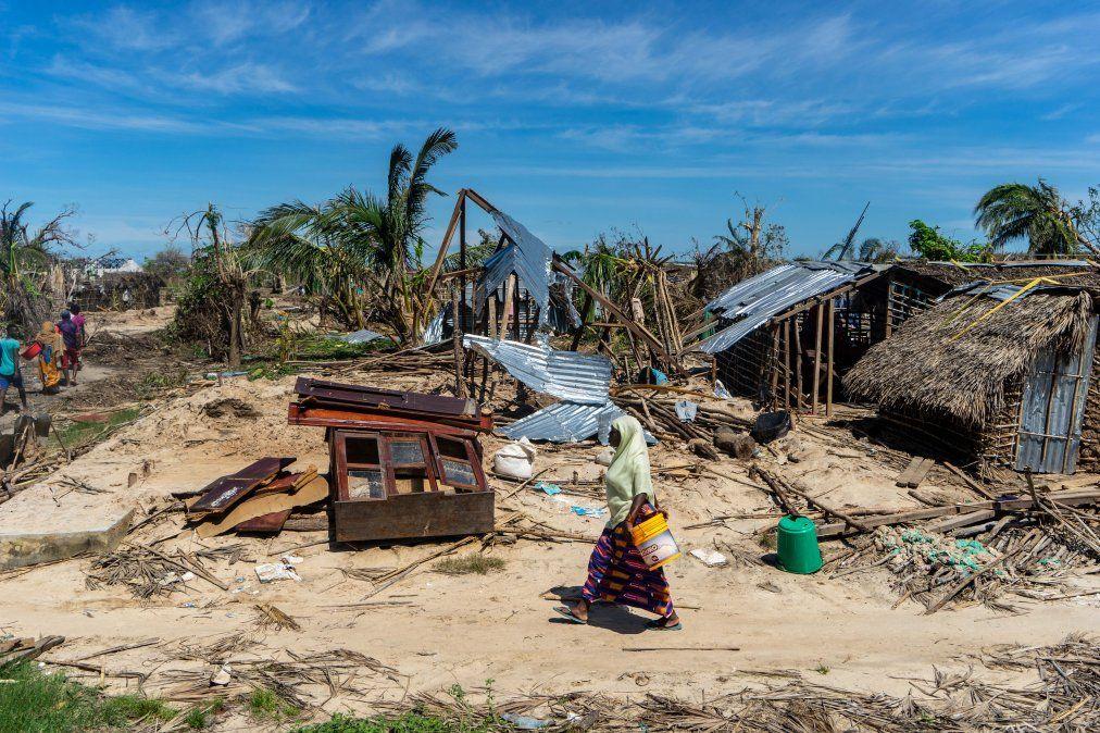 Una mujer camina pasando por casas destruidas rumbo a un centro de distribucuión de ayuda en la villa costera de Guludo en Mozambique