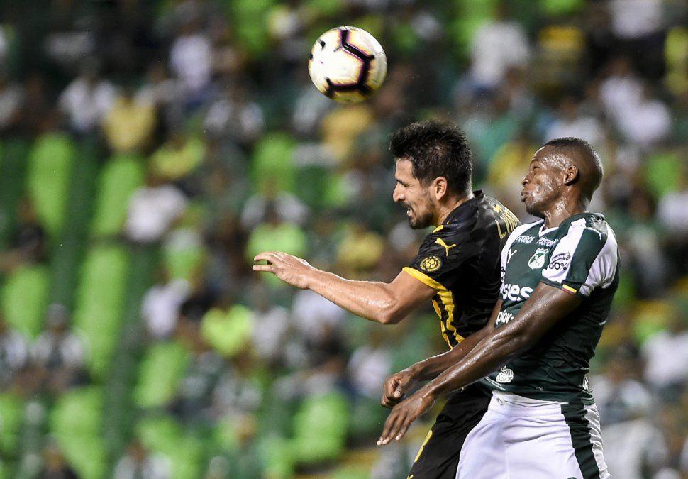 Lucas Viatri disputa la pelota con Richard Rentería. Ambos volverán a verse las caras en el partido de vuelta en Montevideo entre Peñarol y Deportivo Cali.
