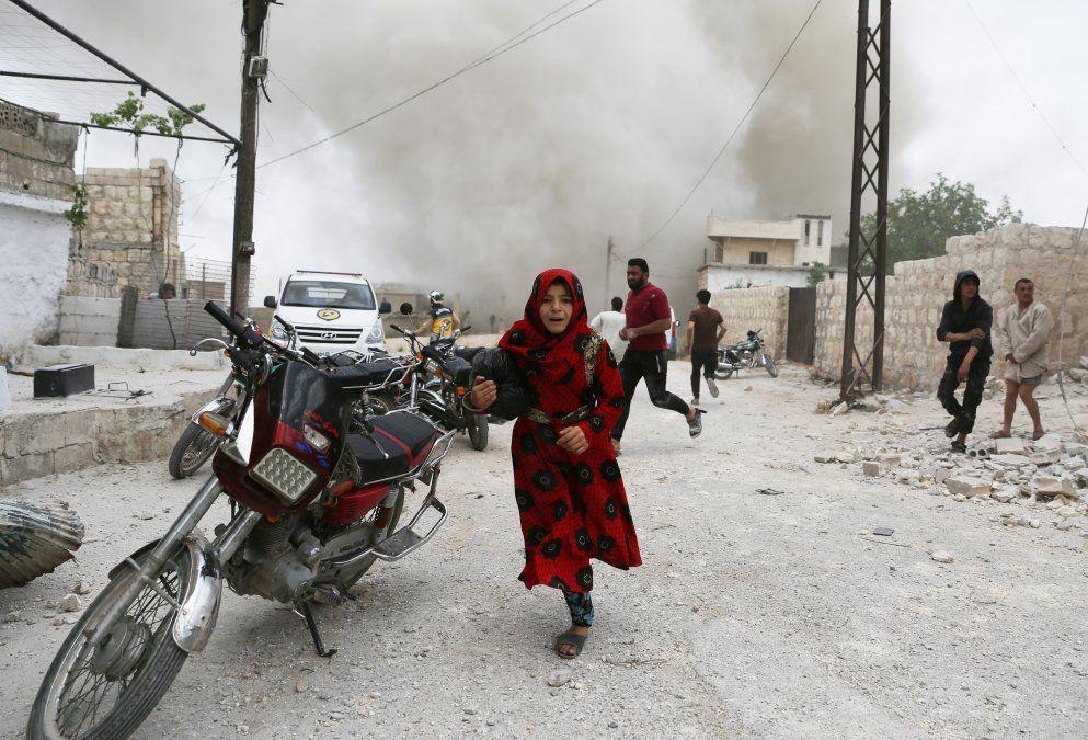 Los sirios corren a esconderse durante un ataque aéreo de las fuerzas pro régimen en la ciudad de Kfar Ruma