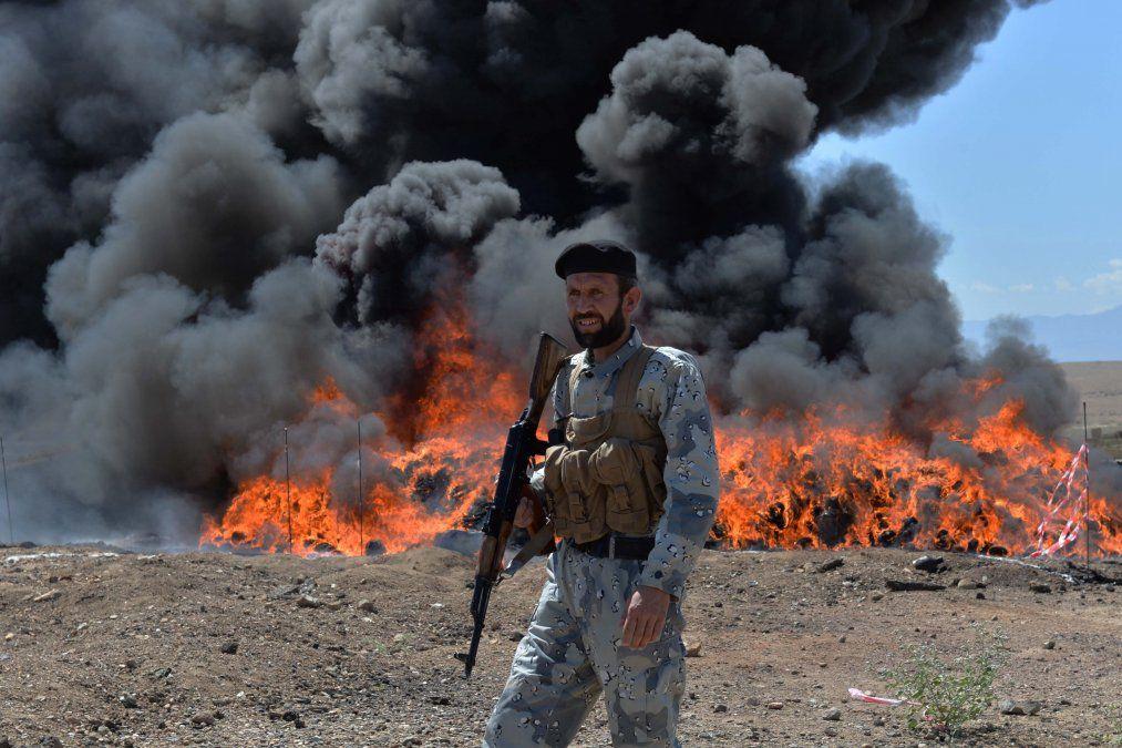Un hombre afgano de seguridad hace guardia cuando queman drogas y bebidas incautadas